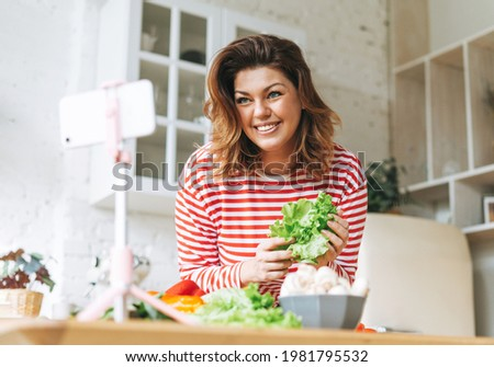Gorgeous young woman plus size body positive in red longsleeve records cooking process on phone camera at home kitchen. Smiling woman food blogger do video stream on mobile on tripod