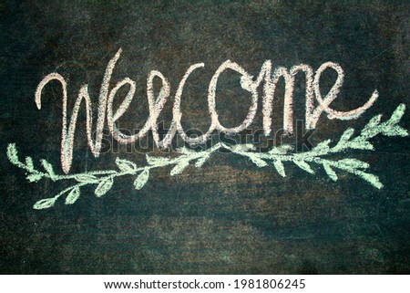 """Handwritten text of """"welcome"""" with chalk on the chalk board"""