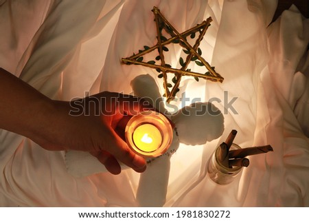 Casting a voodoo spell on a doll to heal spiritual normalcy. This picture is suitable for use in composing articles on magic.