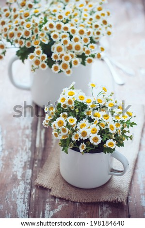 Two vintage enamel mugs with chamomile flowers on wooden background, cozy home rustic decor, cottage living #198184640