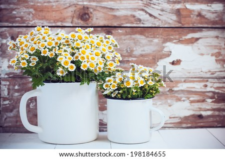 Two vintage enamel mugs with chamomile flowers on wooden background, cozy home rustic decor, cottage living #198184655