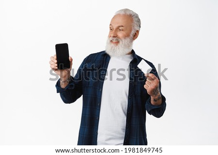 Happy senior man holding bank credit card, looking satisfied at mobile phone blank screen with your app or shopping webpage, standing against white background