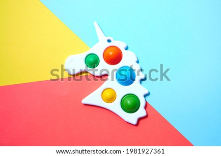 Simple dimple in form unicorn on colorful yellow, red and blue background. Royalty-Free Stock Photo #1981927361