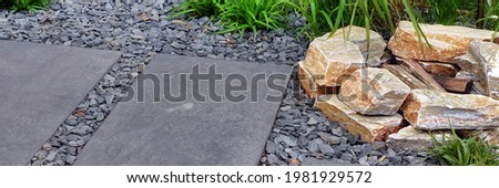 Fireplace from Limestone in Designed Alpine Backyard Garden with Tiled Footpath. Stone Fire Pit from Stone with Firewood near Garden Path from Tiles and Gravel. Landscaped Backyard Design. Royalty-Free Stock Photo #1981929572