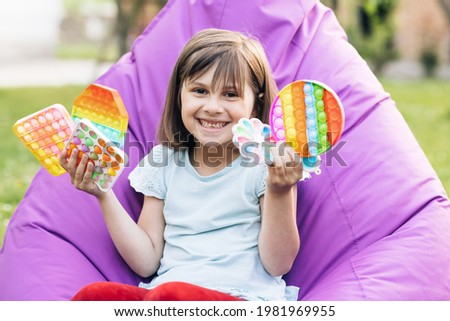 Portrait little girl with a modern popit toy. Colorful and bright pop it toy. Simple dimple. The child is sitting on a easy chair with colorful trendy antistress sensory toy pop it and simple dimple Royalty-Free Stock Photo #1981969955