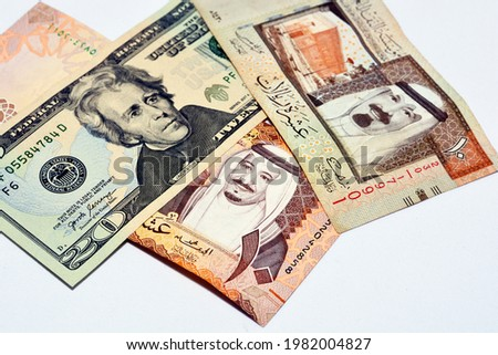 American 20 dollars with Saudi Arabia riyals currency banknotes of 10 Saudi Riyals with photo of king Salman and 10 Saudi Riyals with the photo of king Abdullah, American money and Saudi riyals rates.