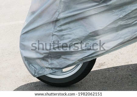A fragment of a motorcycle in the parking lot, covered with a protective film Royalty-Free Stock Photo #1982062151