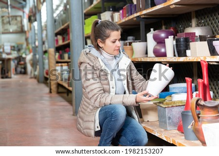 Female seller is standing near clay pots in stock. High quality photo