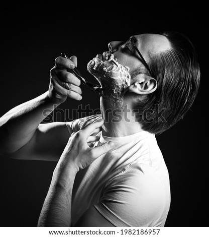 Black and white. Portrait of adult man in white t-shirt and glasses shaving with razor blades and shaving gel foam over dark background. Side view Royalty-Free Stock Photo #1982186957