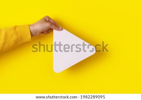 hand holding media player button icon over trendy yellow background Royalty-Free Stock Photo #1982289095
