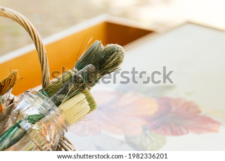 detail of various paintbrushes and brushes stained on restored wooden furniture. restoration of furniture and crafts. carpentry business. Art.