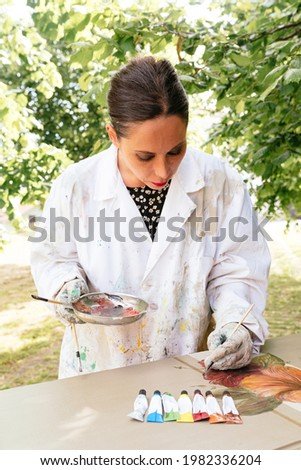 young latin woman painting and restoring an old wooden furniture. Artist holding a color palette and using the paintbrushes from it to draw on wooden surface. restoration and carpentry business.