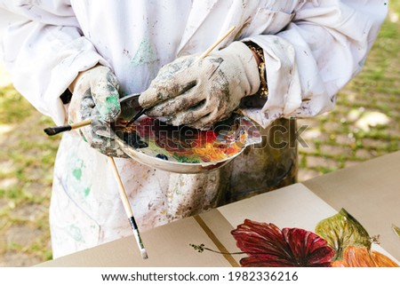 Unrecognizable person restoring and painting a wooden furniture. Painter's color palette detail. Artist working. carpentry business.