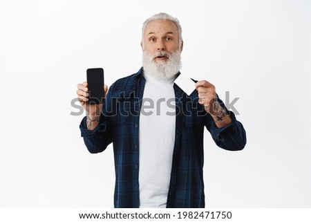 Amazed senior man with credit card, showing smartphone screen and look excited, recommending online shopping app, order delivery on mobile phone, standing over white background