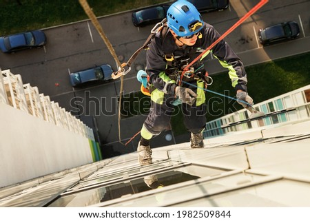 Industrial mountaineering worker hangs over residential facade building while washing exterior facade glazing. Rope access laborer hangs on wall of house. Concept of urban works. Copy space for site Royalty-Free Stock Photo #1982509844