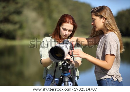Photography teacher teaching to a student how to use a dslr camera in the mountain