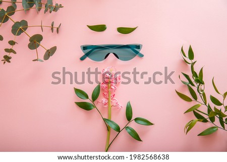 Creative concept female face made of sunglasses spring summer flowers on color summer background. Female Cartoon Face in colored green sunglasses. Top view flat lay