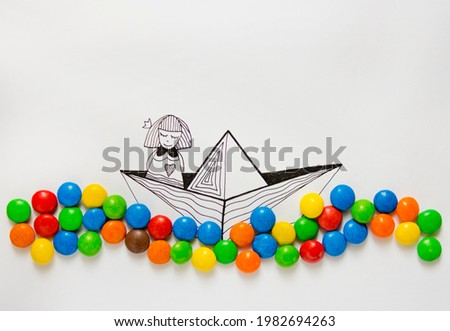 An illustration of a girl floating in a boat in a sea of real colorful candies
