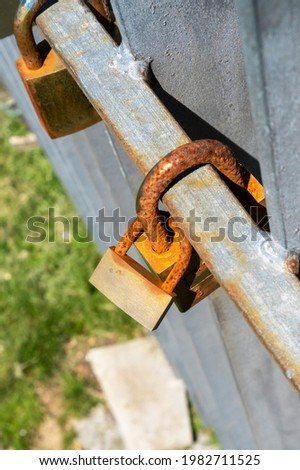 Two rusty old linked padlocks on a bridge beam as a symbol of love and devotion. The concept of eternity and happiness forever