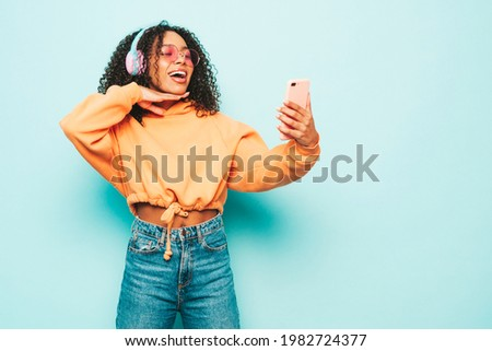 Beautiful black woman with afro curls hairstyle.Smiling model in orange hoodie and jeans.Sexy carefree female listening music in wireless headphones.Posing in studio near blue wall.Taking selfie
