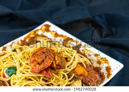 A picture of spaghetti with tomato sauce on a white plate. The tomato is a real Italian recipe with shrimp.