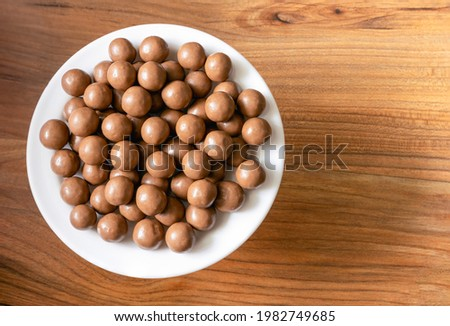 Maltesers milk chocolate balls on a plate on a pine tree surface, top view Royalty-Free Stock Photo #1982749685