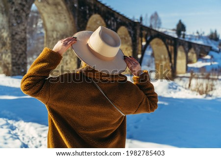 Headdress. A woman in a headdress on the background of the viaduct bridge. Royalty-Free Stock Photo #1982785403