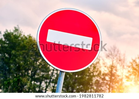 No Entry road sign agains the sky. The road is closed red round sign. White brick in red circle road sign.