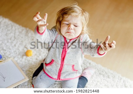Sad crying toddler girl learning painting with felt tip pens. Little baby child drawing on hands and clothes. Angry child in hysteric crisis as parents scold with daughter for dirty hands.
