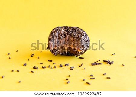 Chocolate brigadier on yellow background. Royalty-Free Stock Photo #1982922482