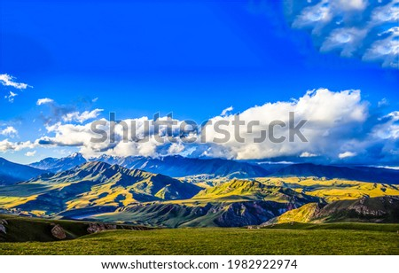 Blue sky with clouds over a hilly mountain valley. Mountain hill valley panorama. Mountain hills landscape
