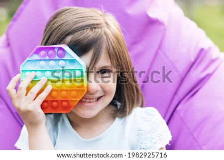 Colorful and bright pop it toy simple dimple. Trendy antistress sensory toy fidget push pop it and simple dimple in kid's hands. Close up of portrait little girl with a modern popit toy. Royalty-Free Stock Photo #1982925716