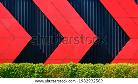 Front view of red arrows pattern on black corrugated metal wall behind green bush fence in exterior architecture decorations design concept Royalty-Free Stock Photo #1982992589