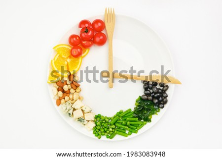 Colorful food and cutlery arranged in the form of a clock on a plate. Intermittent fasting, diet, weight loss, lunch time concept. Royalty-Free Stock Photo #1983083948