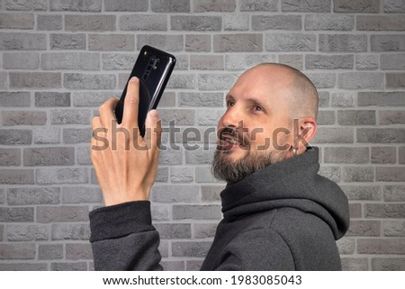 A middle-aged man with a beard and a cute smile takes a selfie on a black smartphone against a gray brick wall