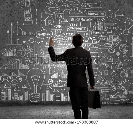 Rear view of businessman looking at chalk sketches on wall #198308807