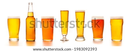 Set of diverse beers in different glasses for clients. Bottle, glass, tall glasses with light tasty cold ale and lager, isolated on white background, empty space, studio shot, panorama, mockup Royalty-Free Stock Photo #1983092393