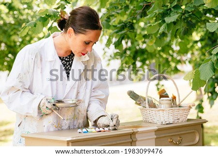 Young Latin woman restoring an old wooden furniture. Restoration of antiques. Hispanic person working in her small carpentry business.