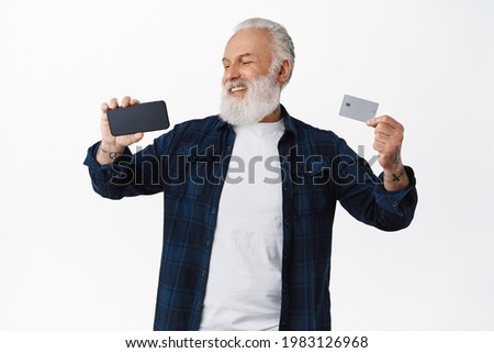 Smiling mature man showing credit card of copyspace bank, looking satisfied and happy at smartphone screen horizontal, standing over white background