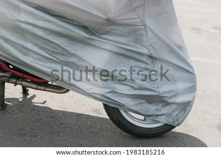 A fragment of a motorcycle in the parking lot, covered with a protective film Royalty-Free Stock Photo #1983185216