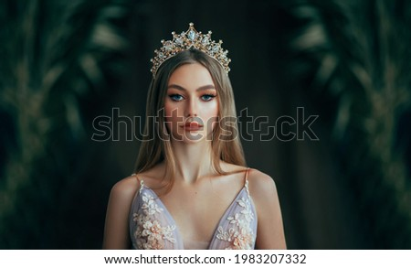 Portrait of fantasy medieval girl princess in dark gothic room. Woman queen looking at camera, beauty face. Vintage trendy glamour dress golden luxury crown, long loose blonde hair. Fashion model. Royalty-Free Stock Photo #1983207332