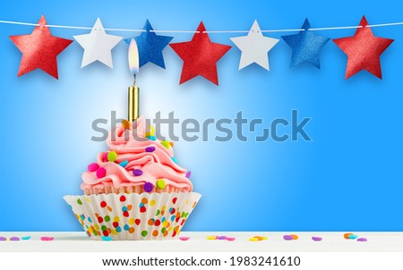 Cupcake and Stars. Happy Birthday, 4th of July, Independence, Memorial or Presidents Day. Tasty cupcakes with pink cream icing and colored sprinkles. Burning candle in a cake. Sweet delicious dessert.