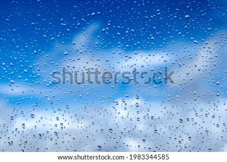 Rain drops on the glass. Beautiful blue and white sky. Sky background Royalty-Free Stock Photo #1983344585