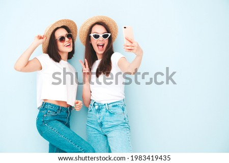 Two young beautiful smiling hipster female in trendy summer white t-shirt and jeans clothes.Sexy carefree women posing near light blue wall in studio.Positive models in hats taking selfie photos