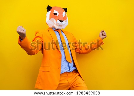 Cool man wearing 3d origami mask with stylish colored clothes - Creative concept for advertising, animal head mask doing funny things on colorful background
