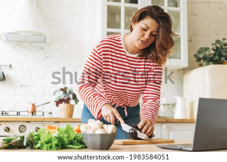 Attractive young woman plus size body positive in red longsleeve cooking food using laptop with online video recipes on kitchen at home