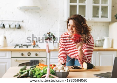 Gorgeous young woman plus size body positive in red longsleeve records cooking process on phone camera at home kitchen. Smiling woman food blogger do video stream on the mobile on tripod