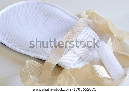 A restraint mitt or hand control glove with Velcro belt and straps to secure onto patient's hand in order to prevent patient from scratching or picking at wounds, removing IV lines or feeding tubes. Royalty-Free Stock Photo #1983652091