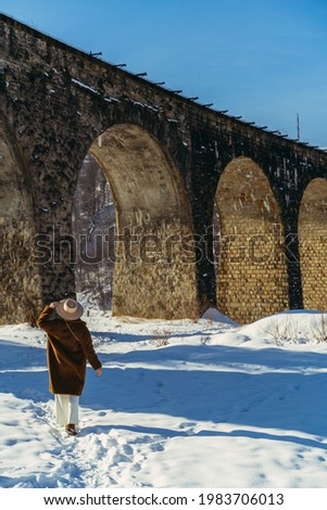 Headdress. A woman in a headdress on the background of the viaduct bridge. Royalty-Free Stock Photo #1983706013