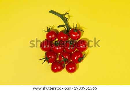 Summer color food background - red cherry tomatoes in sunlight with shadows as berry shape with green tail on yellow backdrop, flat lay,  copy space.